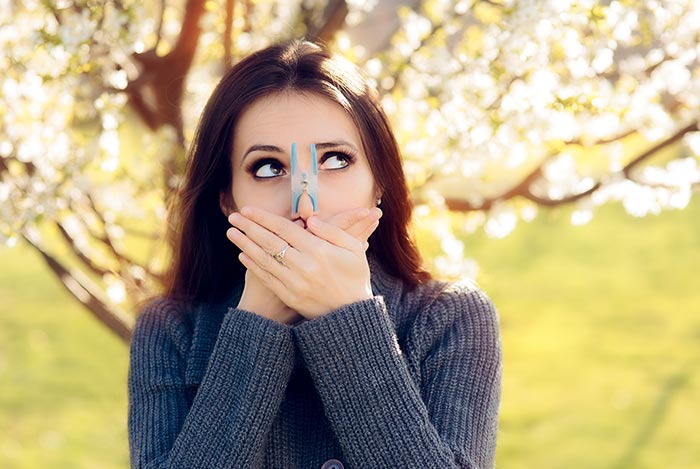 Kobieta z klamerką na nosie unikająca alergii